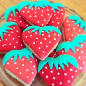 Biscuits in strawberry heart shapes with red and green icing decoration.