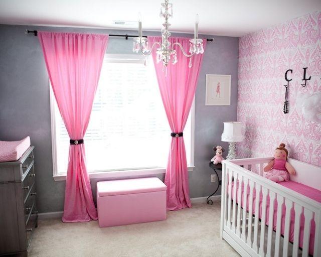 rideaux roses et murs gris dans la chambre de bébé fille