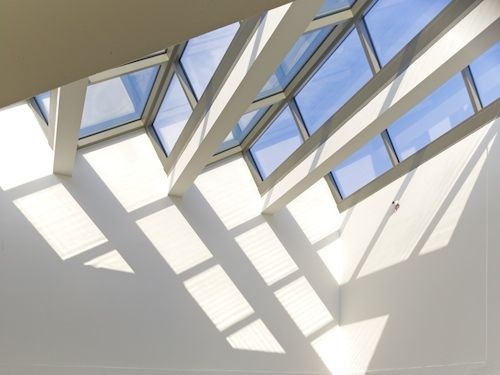 Saw tooth atrium roof that captures natural light from above within the house.