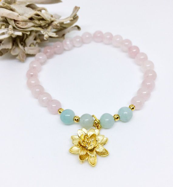 This healing Wrist Mala Beads Bracelet is hand made with Rose Quartz 6mm Beads, 4 Amazonite 6mm Beads and a Lotus Charm on a stretchy string. Keep this healing Yoga bracelet for your self or give it as a Valentines day gift, Birthday Gift, Christmas Gift, Anniversary gift or any other special occasion.  GEMSTONE DESCRIPTION  ♥ The Rose Quartz is a stone of the heart and is said to be symbolic of love and beauty. Its a Crystal of Unconditional Love. It carries a soft feminine energy of…