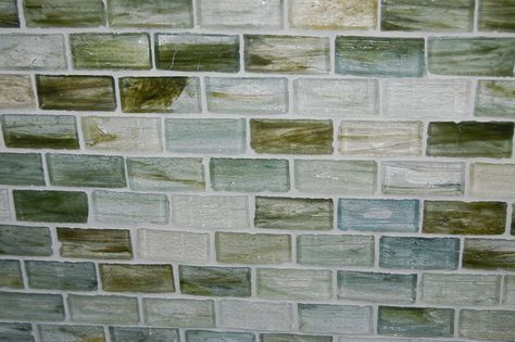 In each tile I see a miniature seascape.  The tile is Sumi-e glass tile by Lunada Bay. The color is Atami natural in the brick pattern. You can see all the color options on their website.
