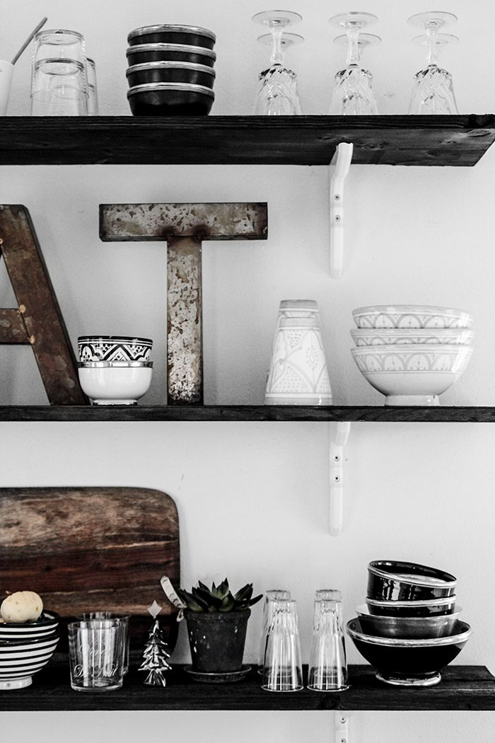 dark kitchen shelves on a white wall. Beautiful accessories and kitchenware