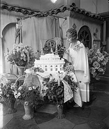 Aimee Semple McPherson surrounded by flowers, cutting into Angelus Temple cake, 1927. Not one for settling into a predictable routine, she used her birthday, national holidays and other events to theme church services and gala festivities around.