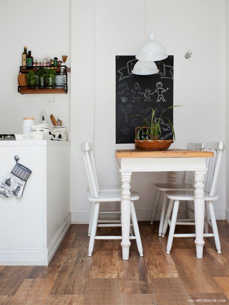 Cozinha iluminada com móveis brancos, parede de lousa e piso de porcelanato que imita madeira.