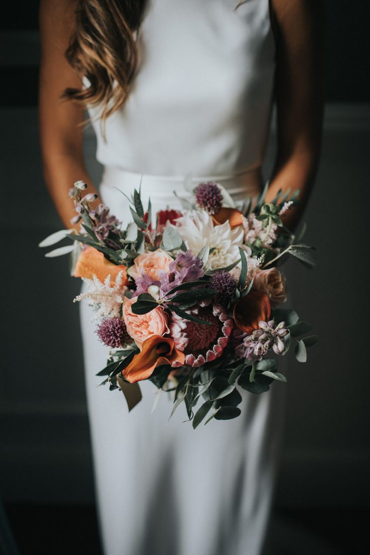 Deep Red & Oranges Bridal Bouquet with Protea - McGivern Photography | Launcells Barton Country House in Bude Cornwall | Elegant Rustic Barn Wedding | Charlie Brear Torum Gown | Ted Baker Suit | Pink Bridesmaid Dresses