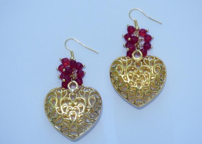 Aretes dorados con cristales rojos facetados y dijes de corazón. AR122