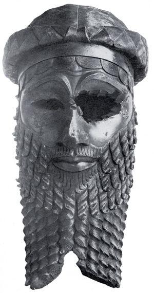 Photographie d'une sculpture en bronze représentant une tête et décrite en détail dans ce paragraphe.
