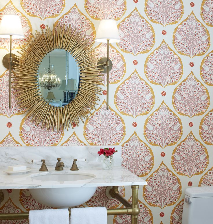 Modern colorful powder room with pink and orange lotus wallpaper from Galbraith and Paul; Arteriors Home modern spikey brass oval mirror; Urban Electric brass wall sconces; unlacquered brass washstand; bianco cararra marble vanity countertop; brass accents in the bathroom; bold color in the powder room