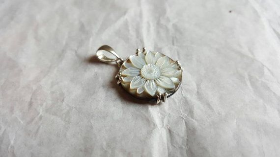 Handmade flower cameo in mother of pearl set in sterling silver.  #donadiojewelry #cameojewelry #flowercameo #pendant