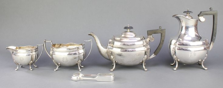 Lot 460, A silver 4 piece tea and coffee set with ebony mounts and pad fee, Sheffield 1919/1920, gross weight 60 ozs, together with a pair of nips est £500-700