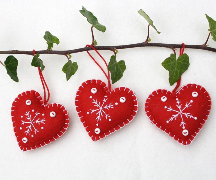 Handmade red and white felt snowflake Christmas ornaments. These Scandi style felt heart ornaments are embroidered with snowflakes and finished with tiny buttons and a loop for hanging. They come in a