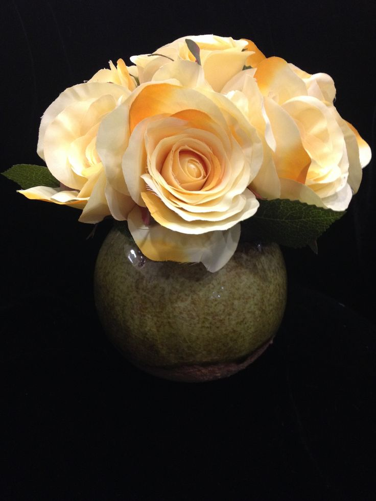 Yellow rose arrangement shown in its ceramic green bowl