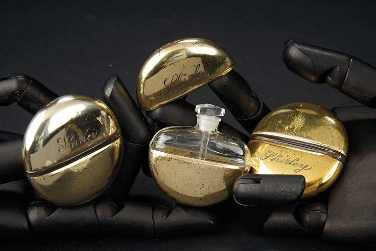 "Liefde, Shirley Temple, Take Two: Van Schoolmeisje naar Storybook: 77 Three Brass-Cased Glass Parfumflessen Getekend ""Shirley"""