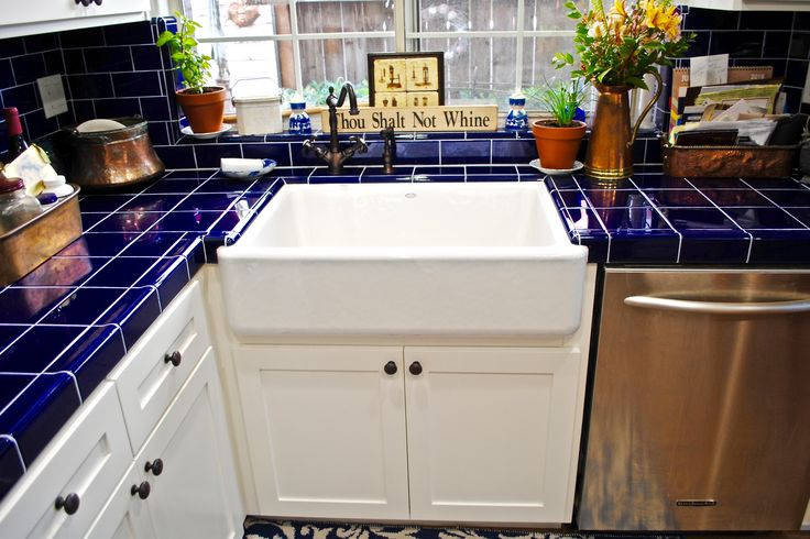Mixing old and new styles can make for an amazing outcome on your remodel. Recently the Farm sink has become a favorite but we wanted to take it a step further by adding a classic cobalt blue tile countertop and a retro faucet.   #FarmSink #TileCountertop #CobaltBlueTile #ShakerCabinets #Remodel #KitchenRemodel #BerryConstruction #BerryConstructionandRestoration