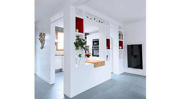 La cuisine est ouverte tout en restant séparée du salon. Elle se découvre en douceur grâce à une cloison semi-ouverte tout en jeu de niches et de touches de couleur.