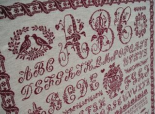 Sampler Clorami de Clorami Designs, brodé en point de croix rouge