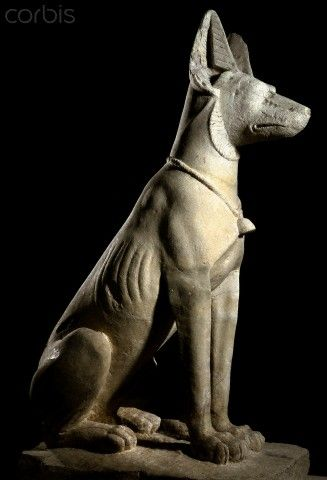 Ancient Egyptian sculpture of a dog wearing a collar with bell