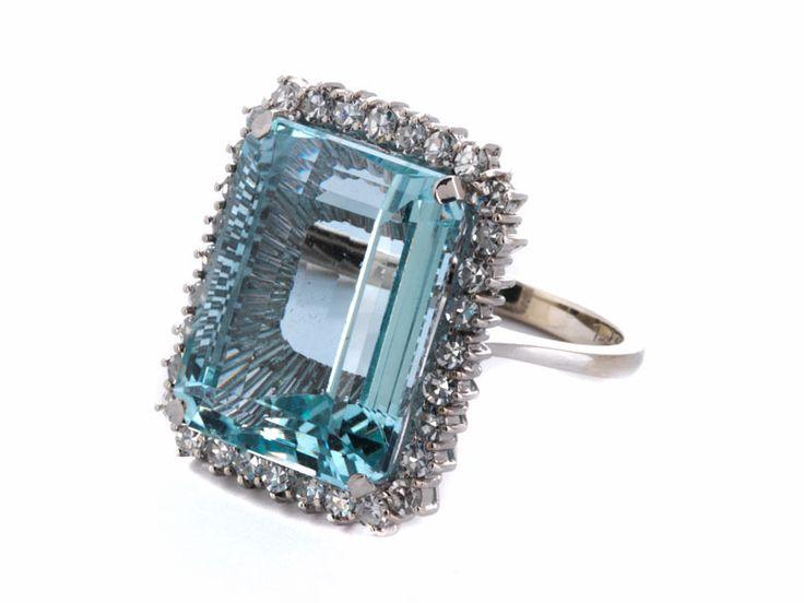 Ringweite: 48/ 49. Gewicht: 9,2 g. WG 750. Klassisch-eleganter Ring mit zentralem Aquamarin im Smaragdschliff, ca. 15,8 ct, umrahmt von kleinen Brillanten, zus....