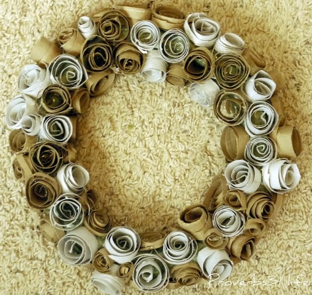 she cut toilet paper holes in thirds / cut them into spirals / curl them back around on themselves to make little rosebuds / hot glue to wreath form / can spray paint