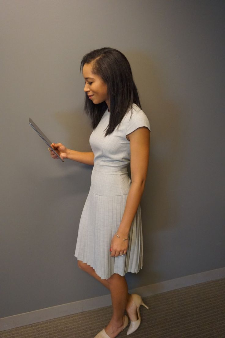 woman wearing grey work dress with pleats, skirt the ceiling skirttheceiling.com