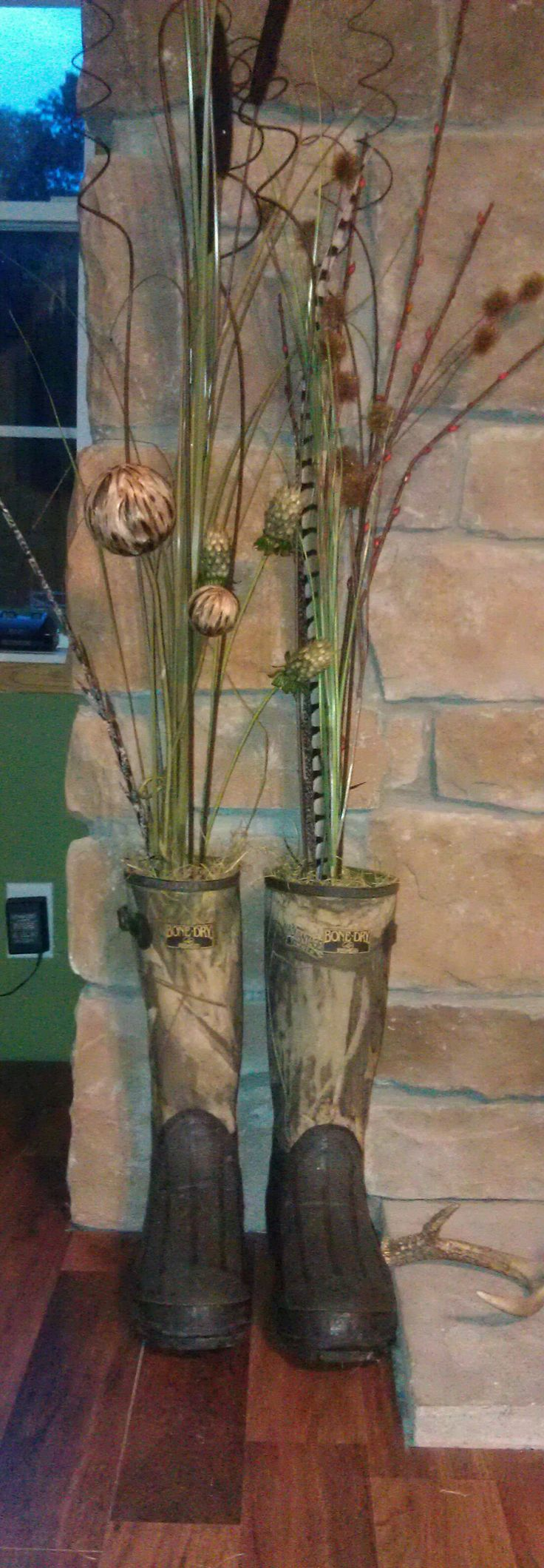 This is my own personal creation. My grandfather passed away in January and he was an avid hunter, as is my husband. No one in our family could wear his hunting boots that were practically brand new so I took them and them a decoration for Chris' hunting room. I stuffed them newspaper  and styrafoam and then added the greenery from Hobby Lobby. (waited til it was 50% off)