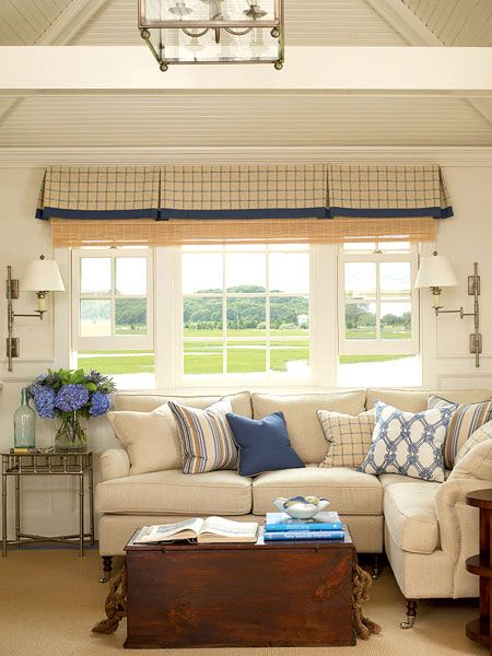 A plush sectional fitted into a corner gives maximum seating in minimum space. A mostly neutral palette is accented with navy blue cushions, a valance, and accessories. (Photo: Tria Giovan)