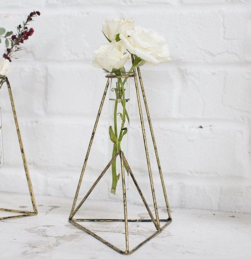 Get modern geometric floral vases for your home decor like this triangular metal stand from the Vector Collection. Place your favorite silk flowers in the glass tube vase and display the stand on a si
