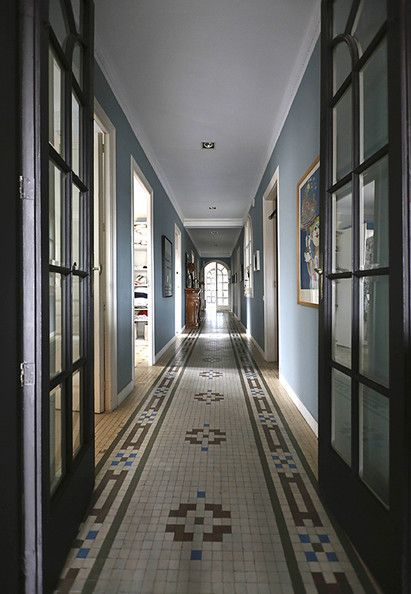 A long and narrow hallway of detailed mosaic tile flooring in the home of Georg Kayser.  Click through for the full story!