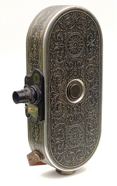 The beautiful Filmo 75 is a 16mm movie camera, produced in Chicago beginning in 1928. It was intended for amateur use, but the quality of its construction makes it easy to see why Bell & Howell cameras were the tools of choice for Hollywood studios in the early days of motion pictures.    Although rather heavy by today's standards, the 75 was quite compact for its time, and was marketed as a ladies' camera. Its ornate leather covering was available in Walnut Brown, Ebony Black, and Silver…