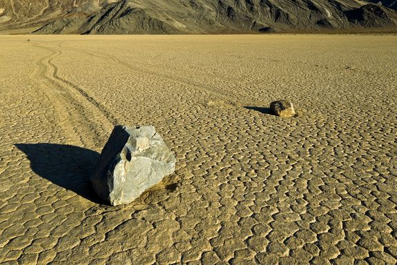 """Mystery of the sailing stones SOLVED: In 2006, NASA scientist Ralph Lorenz used items he had around the house and  discovered how the stones """"sail"""". After rain or heavy dew, a thin sheet of ice forms on the ground, surrounding the rocks. As the ice thaws, friction causes the ice encased stone to slide over the mud! Night time in the open desert can drop to freezing quite easily under the right circumstances, such as after a light rain!"""