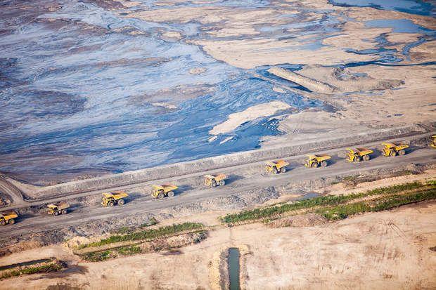 La valse des énormes camions CaterpillarLes énormes camions Caterpillar, capable de transporter jusqu'à 400 tonnes de matières premières dans leur bennes, attendent d'être chargés dans une carrière de sables bitumineux. En arrière fond, un bassin de décantation où stagnent les résidus boueux de l'exploitation des hydrocarbures.