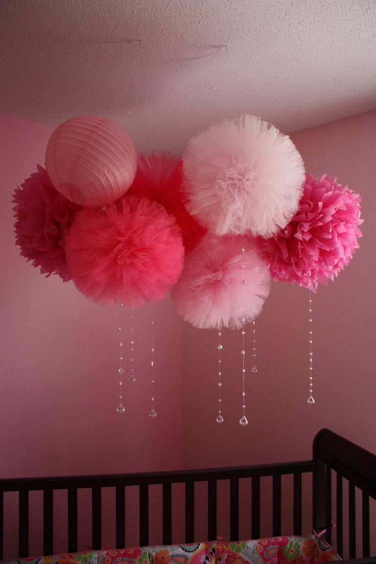 Tulle pom poms for a centerpiece on the ceiling, and streamers of various pinks flowing from them.