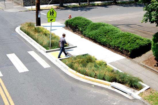 Rua verde em Portland. Combina um sistema de tratamento de águas pluviais com um bulbout [aumento da calçada] para acalmar o tráfego e reduzir a distância travessia de pedestres.
