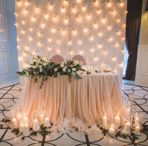 27 Cool Sweetheart Wedding Table Backdrops To Try: a draped blush fabric backdrop with lots of lights perfectly matches the table decor and looks cute #brideandgroom; #weddingreception; #weddingtables; #weddingbackdrop