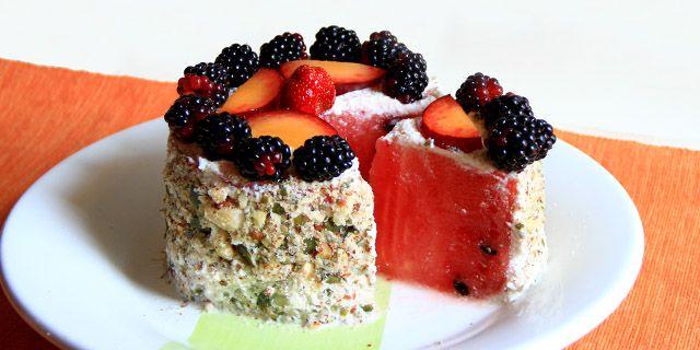 Una torta di anguria con panna di mandorle, frutta e croccantini. Raw watermellon cake.