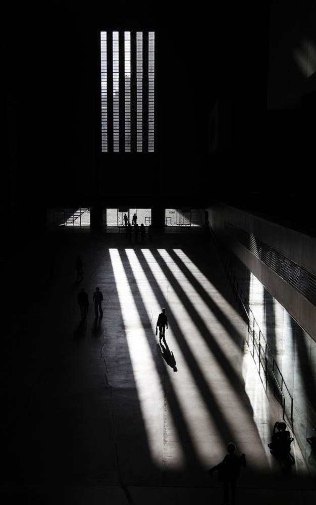 Visitors to Tate Modern walk through sunlight shining through the windows, in London