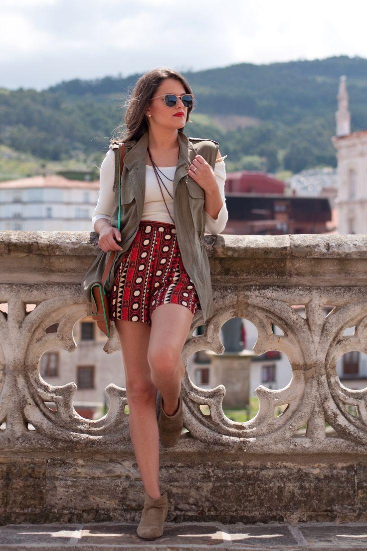 Chaleco militar, camiseta beige, short con estampado naranja, marrón, negro y blanco, botines de ante bajos, bolso marron y gafas de madera. Outfit ideal para primavera y verano