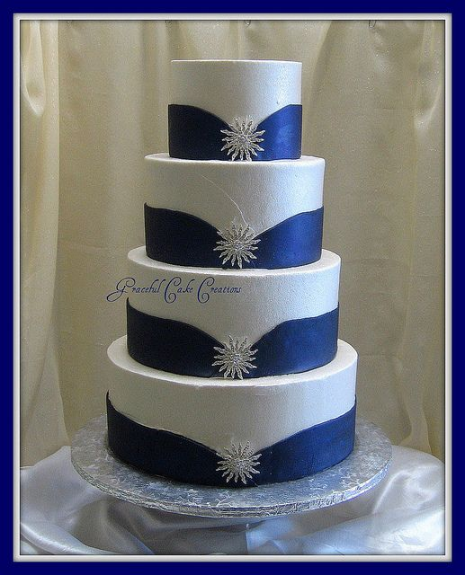 White and Blue Wedding Cake with Silver Jewelry by Graceful Cake Creations...So loving this cake, not my color blue but I like the cake idea and I would replace the suns with my 2 heart theme