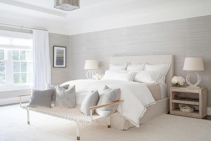 Lit by a scalloped flush mount fixed to a tray ceiling, this gorgeous white and beige bedroom boasts a white woven bench topped with gray pillows and positioned on a cream rug in front of a bed supported by a tan linen headboard matching a tan linen bedskirt complementing white and tan hotel bedding.