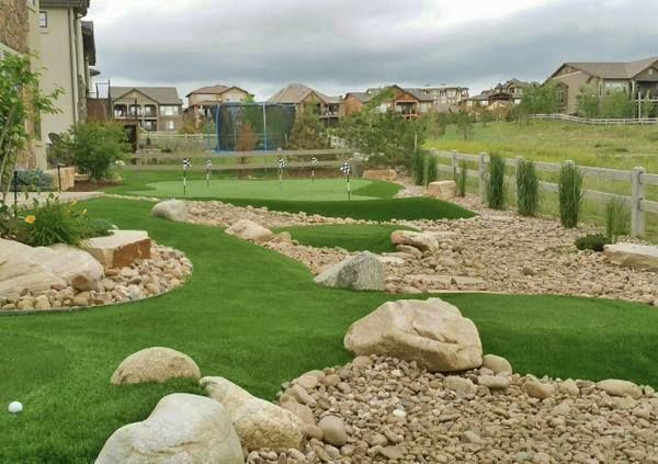 PlushGrass/Celebrity Greens Colorado backyard, sand-filled artificial putting green with multiple tee boxes built into the surrounding landscape.