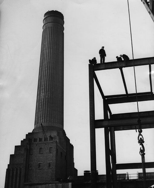 1951: Construction workers stand on scaffolding at Battersea Power Station, doubling the size of the station and adding two chimneys