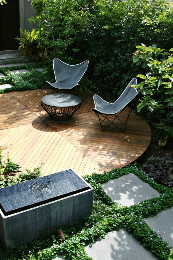 Summer style!! Mid century Modern - Modern contemporary outdoor garden decor! Wonderful ROUND wood veranda terrace patio deck with classic outdoor garden butterfly chairs and a very modern fountain!! Also love the groundcover growing between the concrete stone pavers too!