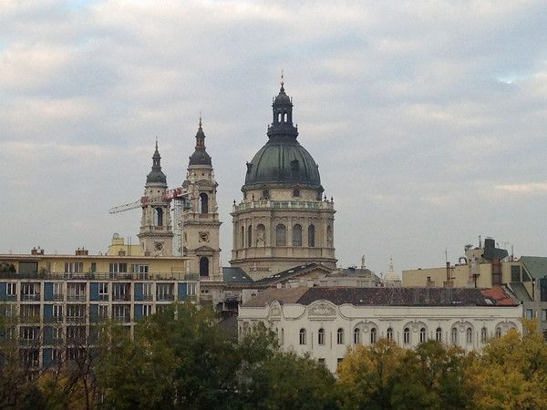 The imposing dome of Saint Istvan's Basilica rises above adjacent buildings and the trees of nearby Elisabeth Ter in Budapest, Hungary.