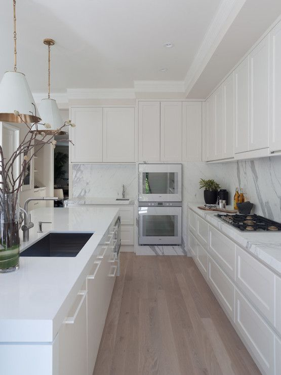 Stunning kitchen with creamy white cabinets paired with calcutta ora marble countertops, calcutta ora backsplash and small prep sink next to Gaggenau Ovens. Concealed kitchen hood is hidden behind faux cabinets over integrated gas range across from white kitchen island accented with thick white countertops and sink illuminated with Visual Comfort Lighting Goodman Hanging lamps over white oak floors.