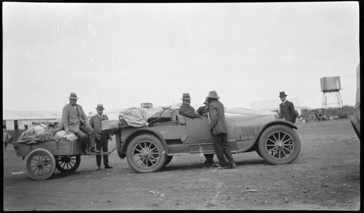304886PD: Group of men with a car attached to a trailer, possibly in Western Australia, ca. 1920. http://purl.slwa.wa.gov.au/slwa_b3807801_2