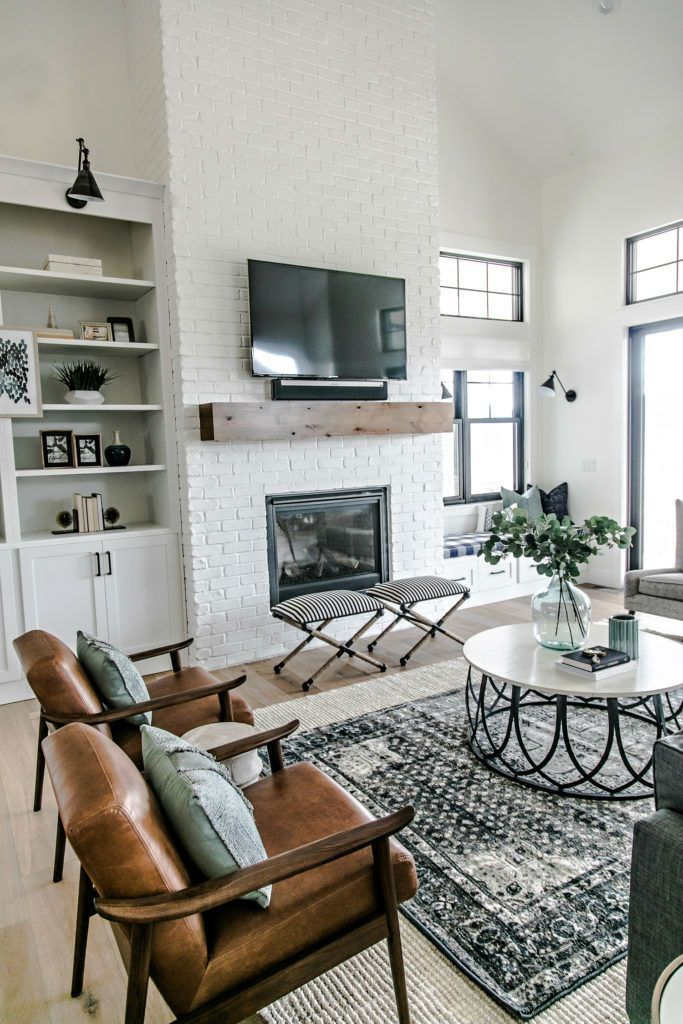Towering white brick walls alongside built-in window seats and a neat shelf creates the focal point in the living room.