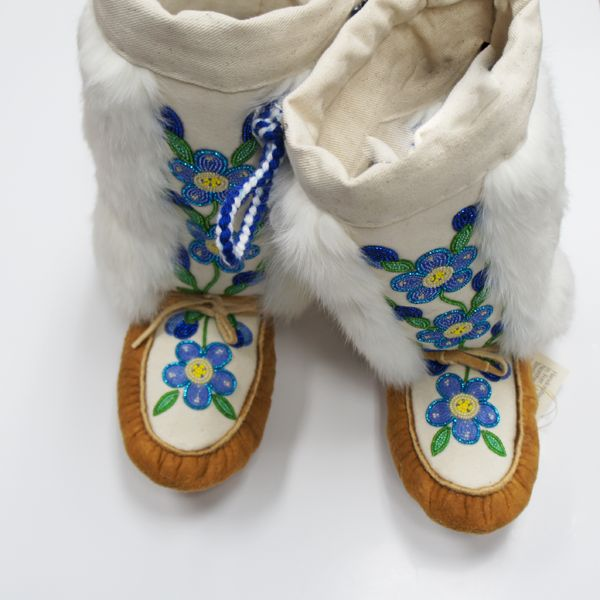 Showcase genuine Aboriginal fashion while staying warm and protected from the elements with these one of kind handmade Mukluks.  Made entirely of Moosehide and wrapped in white rabbit fur. Featuring a hand beaded purple and blue flower design, this one of kine piece is made by Northern artisans in Fort Liard, Northwest Territories.  Buy online today.Men's size 7, women's size 8.