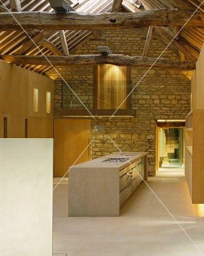 im designerstil ausgebauter offener wohnraum mit freistehendem kchenblock vor natursteinwand