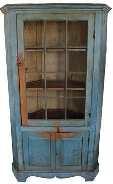 Corner cupboard over two raised panel door with a wide bracket base