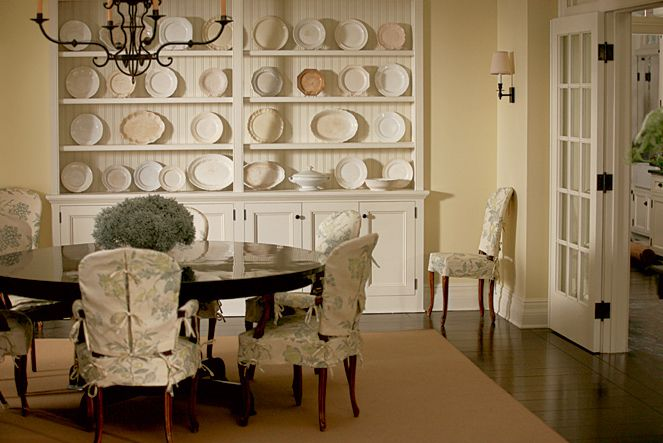 Such a beautiful dinning room ~ love the chair slipcovers & the wall units with the creamware collection ~